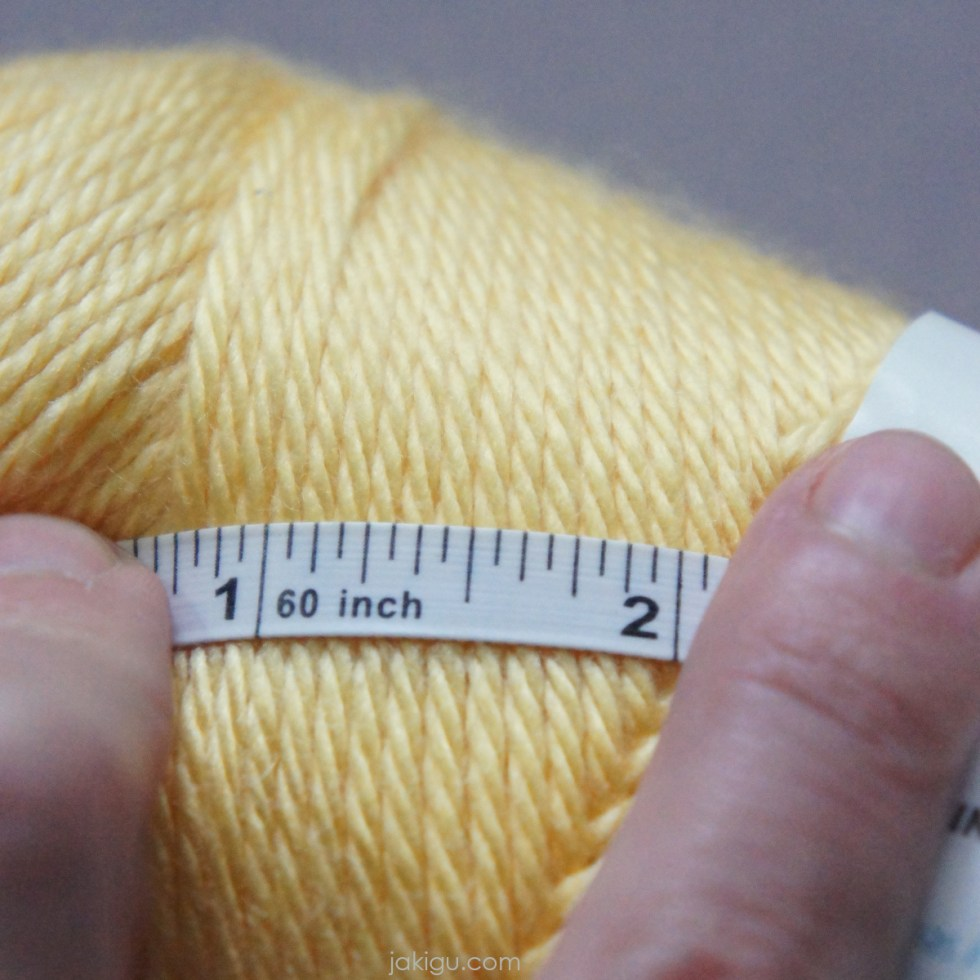 wpi: the tape measure method | jakigu.com | white tape measure held with two fingers on top of a skein of yellow yarn