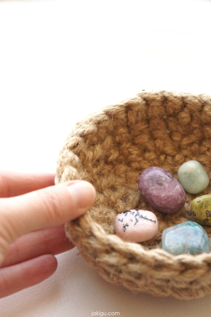 tiny crochet bowl with stones, held by a hand
