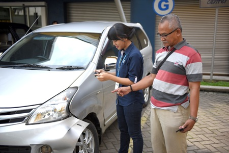 Proses pendataan kerusakan melalui aplikasi garda mobile otosurvey oleh petugas lapagan Asuransi Astra. (istimewa)