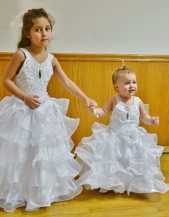 Adorable flower girls, dressed in beads and ruffles