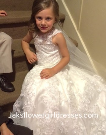Lace flower girl dress with train was designed to match the brides dress.