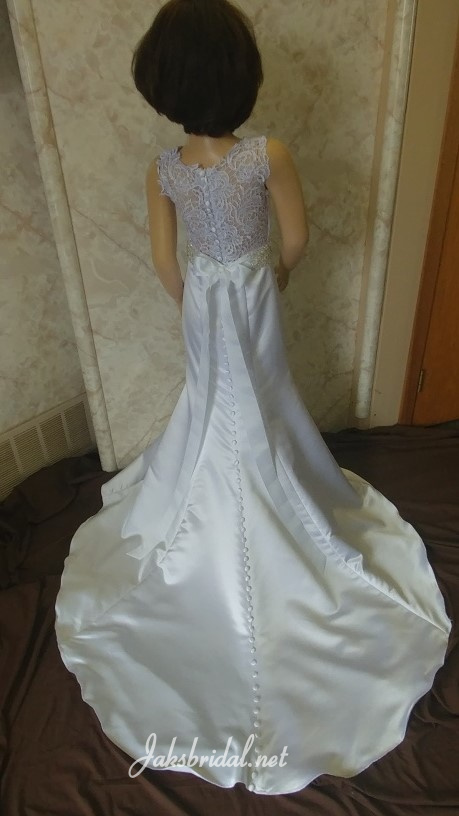 V-neck fit and flare flower girl dress with lace illusion back, silver beaded sash, and covered buttons running down the train.
