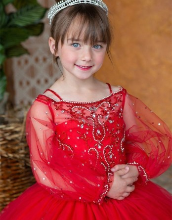 A little girls red pageant ball gown with long sleeves, and beading. Size 3-16.