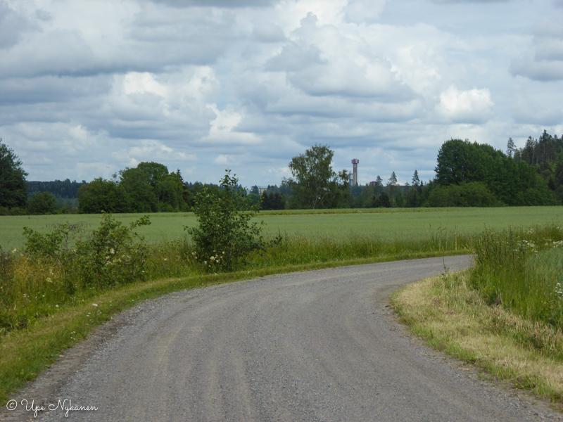 Hyvinkään teollisuusalue pilkottaa pellon takaa.