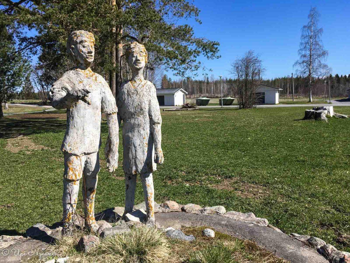 Tyttöä ja poikaa esittävä veistos kristillisen opiston pihassa, Reisjärvi.