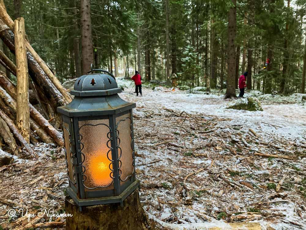 Kynttilälyhty metsäpolun varressa.