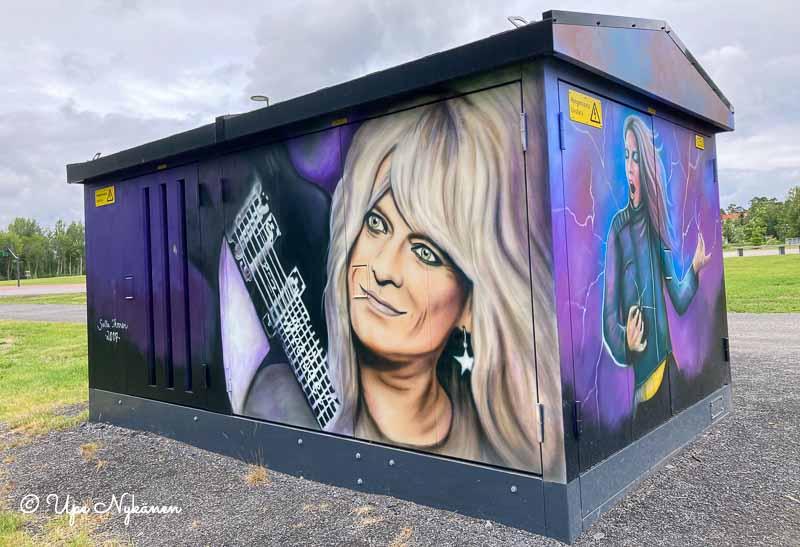 Hanoi Rocksin Michale Monroeta esittävä maalaus ison sähkönjakokaapin seinässä, toisella siculla ilmakitaran soittajatar, Oulu.
