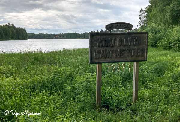 Carola Grahnin taideoteos vuodelta 2016: My name is nature III, Iijoen rannalla puutaulu jossa llukee The River says What do you want me to be.