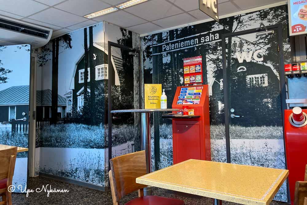Mustavalkoisia valokuvatapetteja Shell Pateniemi-huoltoasemalla, kuvituksena Pateniemen sahan rakennuksista.