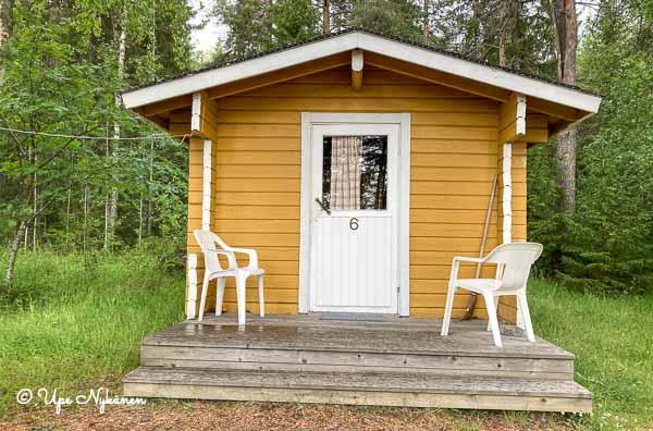 Sinapinkeltainen pieni mökki numero 6 Merihelmi-leirintäalueella.