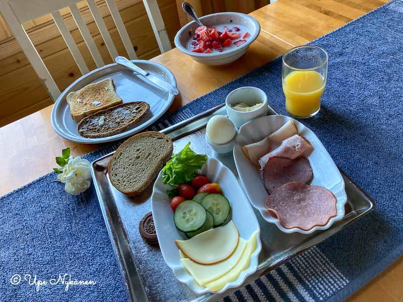Runsas aamiainen Simoniemen makasiinimökissä: leipää, leikkeleitä, mehua, mansikkamaitoa.