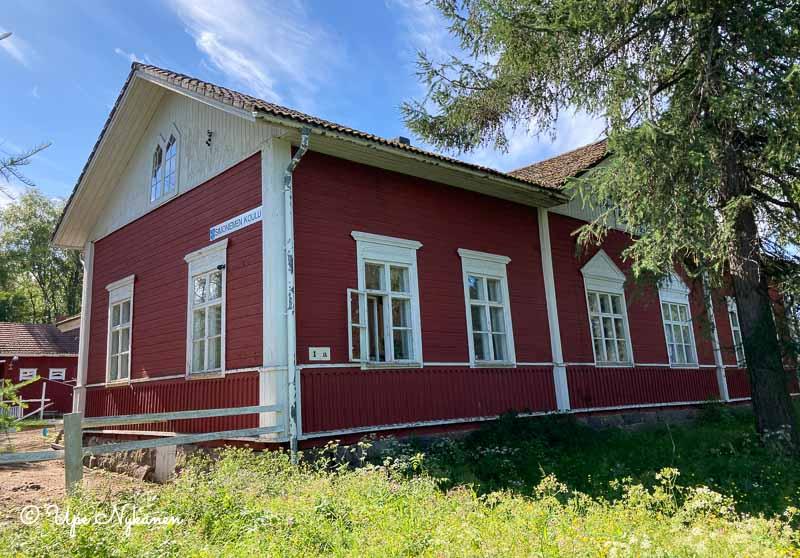 Simoniemen hirsinen, punaiseksi maalattu vanha koulurakennus.