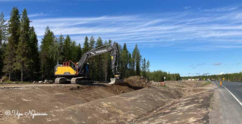 Iso kaivinkone muotoilemassa maastoa nelostien tietyomaan viereisellä rinnakkaistiellä.