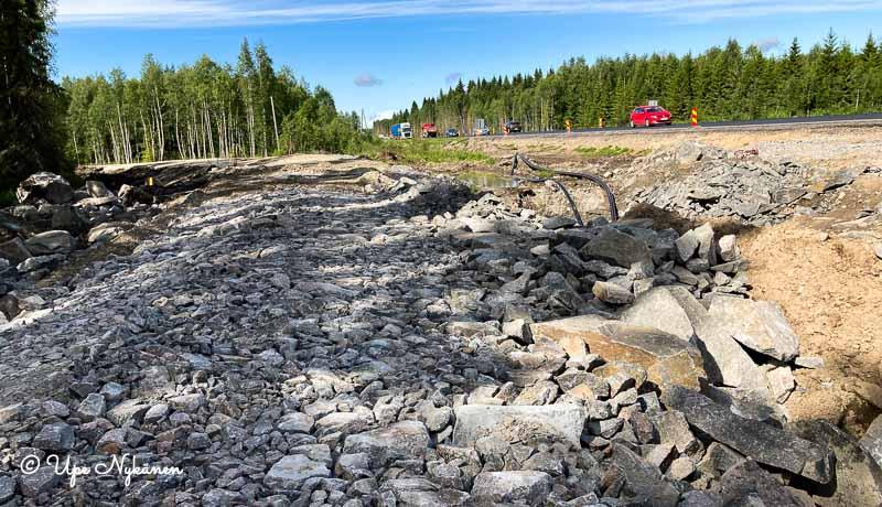 Nelostien viereinen keskeneräinen tienpohja, jonka pintaan on tasoitettu sekalaisen kokoisia kiviä.