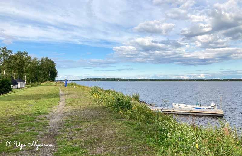 Kemijoen rantatöyräs, jonka nurmella kävelijä ja vene parkissa joen rannassa.