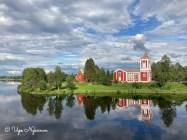 Tervolan kirkko, kellotapuli ja vanha kirkko ilta-auringossa, heijastuu tyynen Kemijoen pintaan.
