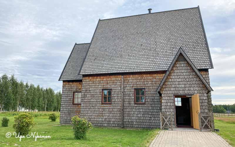 Paanukattoinen ja paanuseinäinen pieni kirkko.