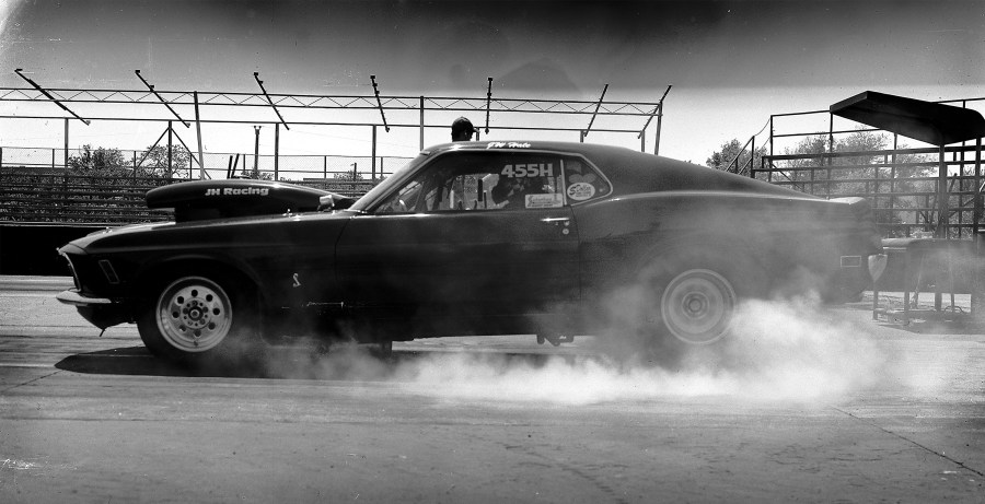 A custom built Mustang muscle car performing a smokey burnout at the Tulsa Raceway Park. Shot with a Toyo 4x5 view camera on black and white film.