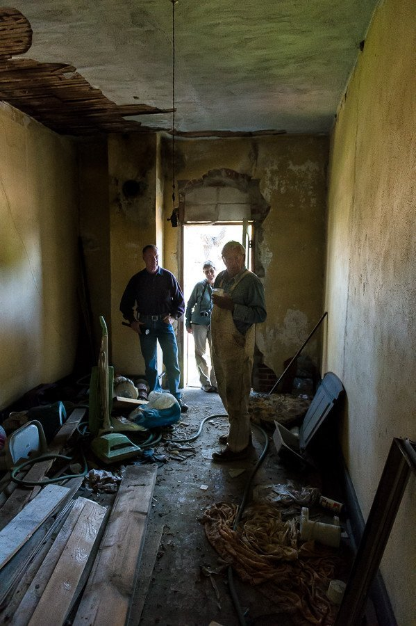 Bud Rose, owner of the Buffington Hotel in Westivlle, Oklahoma shows Bill and Susan Dragoo around the upstairs portion of the dilapidated hotel.