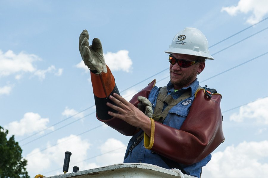 Thick rubber gloves protect lineman from electrical shock while working on live power lines.