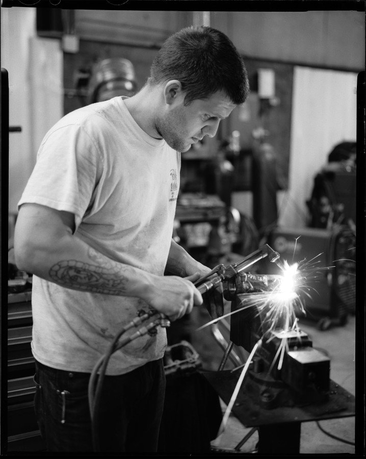 Jimmy Cook cutting metal with a torch at Tombo Racing shop.