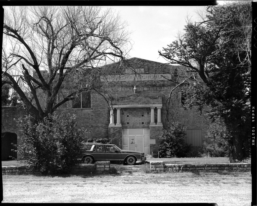 The high school in Martha, Oklahoma sits abandoned with an old station wagon parked in the front yard.