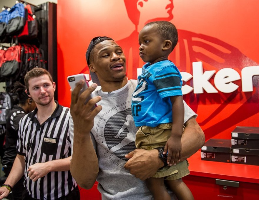 OKC Thunder Russell Westbrook posing for a photo with a young fan.
