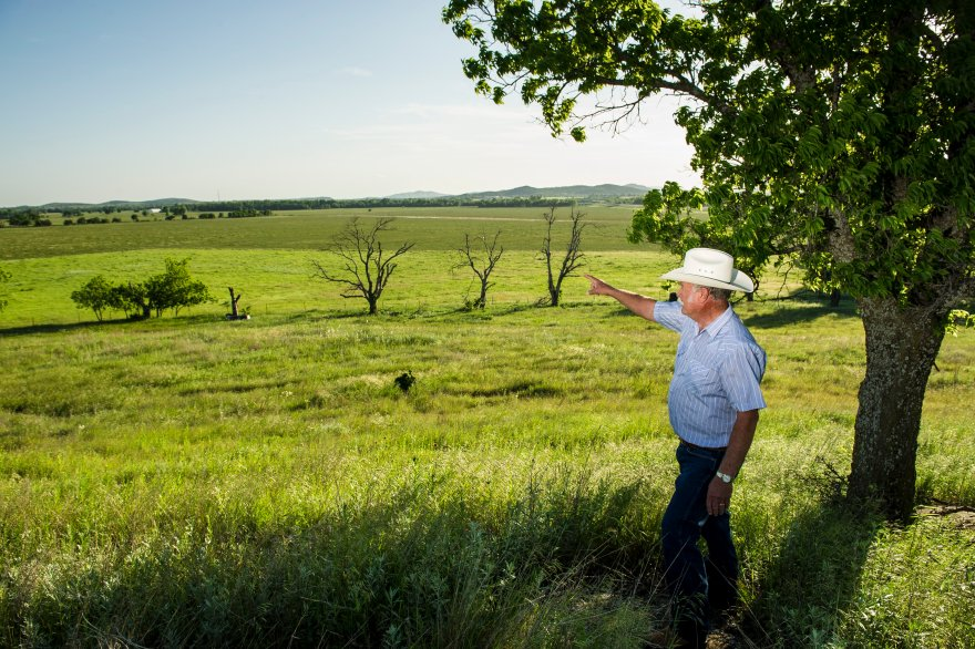Kenneth Goodin pointing out the boundary to his property near Elgin, Oklahoma.