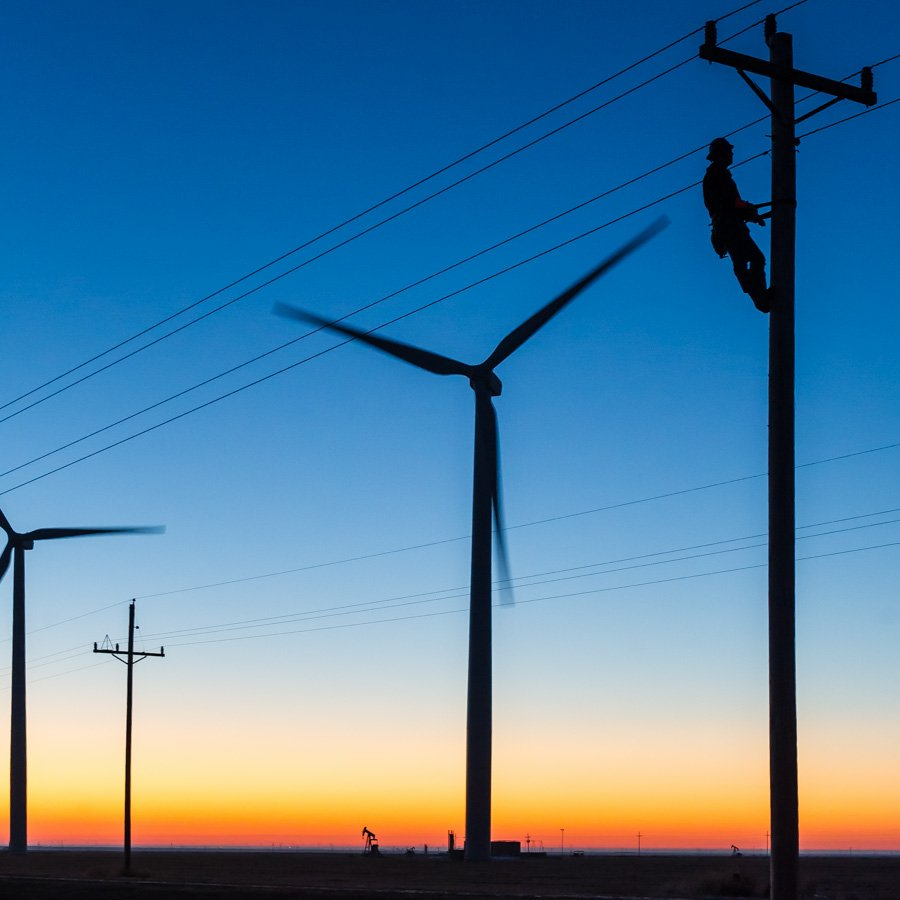 an alectrical lineman works on a pole at sunrise in the Oklahoma panhandle for Tri-County Electric Coop TCEC