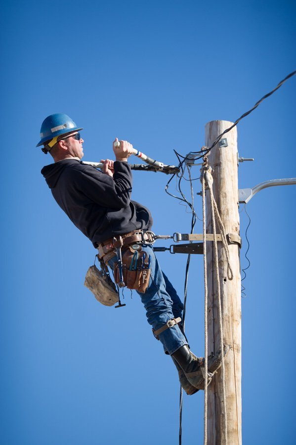 Electrical lineman working on a power pole for Tri-County Electric Coop TCEC