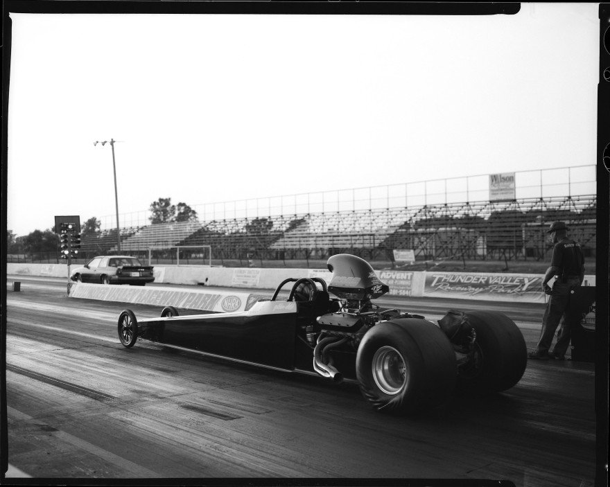 This alcohol rail dragster is going up against a slower car in the right lane. The slower car launches first and gets a head start, and this dragster was just launching when I snapped the shutter on my Toyo VX-125 4x5 film camera. I used a Rodenstock 135mm F5.6 lens for this shot on Ilford HP5 film.