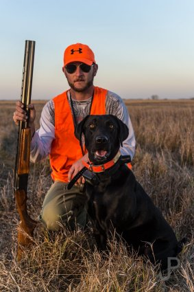 Vance Fielder poses with his black lab Ruger while pheasant hunting in South Dakota.