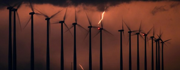 The silhouette of spinning wind turbines is backlit by a bolt of lightning in a thunderstorm at night. Quillete | James Alexander Michie
