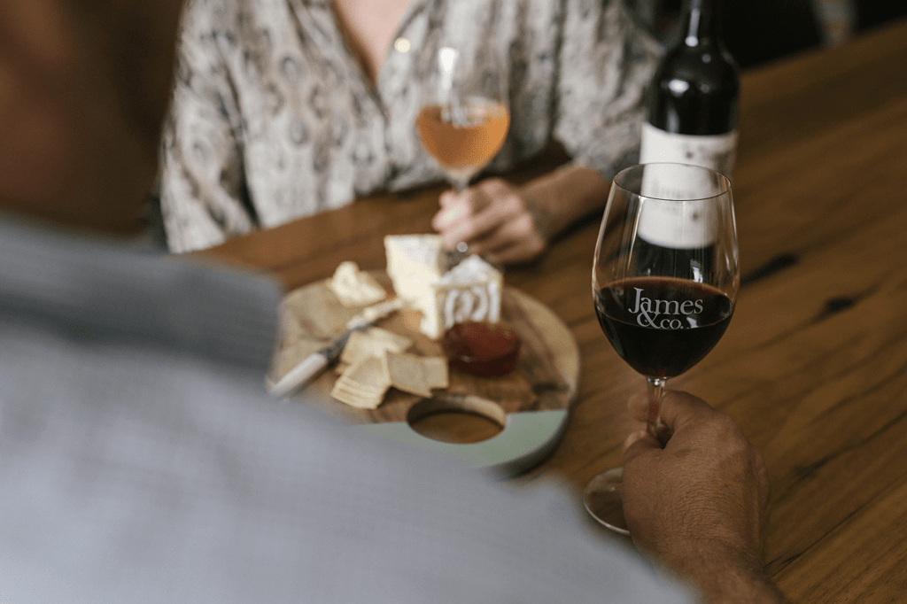 Two people enjoying a cheese board and a glass of red