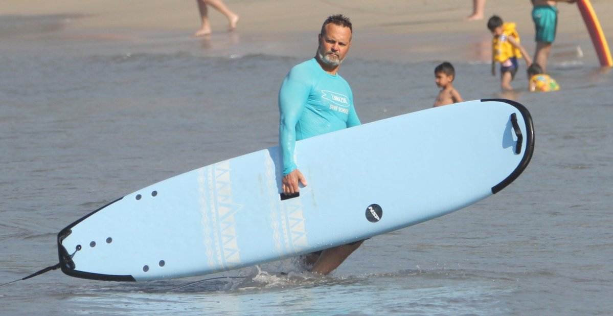 James Chicalo holds a surfboard, standing in shallow water.