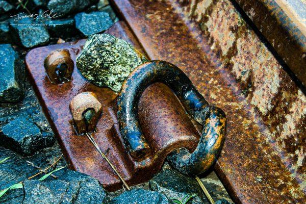 JCCI-100089 - Old rusty rail track clamp on ballast
