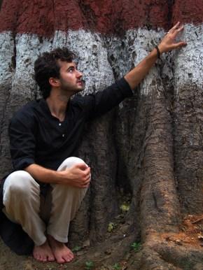 barefoot at the base of a sacred banyan tree, Bangalore, India.
