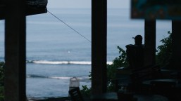 A local relaxes before the start of the working day in the Uluwatu Surfing Village