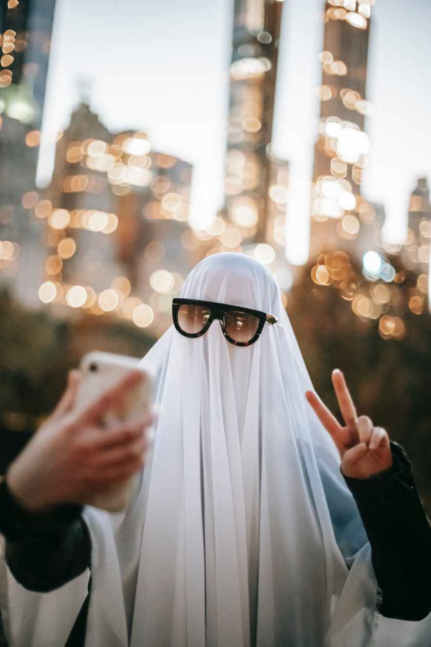 unrecognizable person in ghost costume taking selfie on street