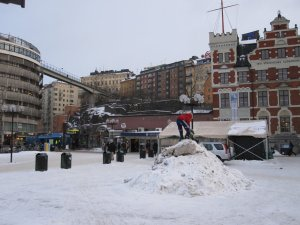 Mother and child playing in the snow at Slussen