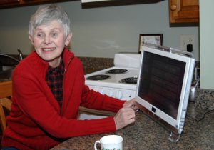 Sandy Kindberg, a resident of the Smartment® Building explains how easy it is to navigate the touch screen interactive computer monitor.  Residents of the Smartment® fill out a simple wellness survey each day that is shared with their personal wellness coordinator. An Open House is planned for Saturday, April 20th from 10:00 until noon.
