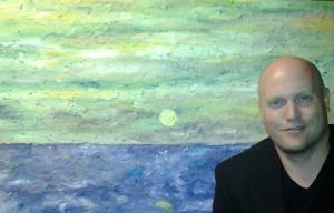 Casey Brink poses in front of a painting titled Easter.  His display at the library will consist of abstracts, textured flowers and landscapes.