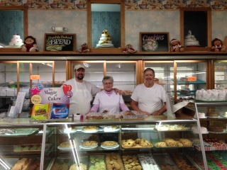 Chad, Suzan, and Richard behind the cases at Ecklof's Bakery.
