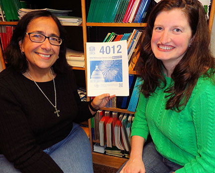 (L to R) Rose Ann Lancione, Volunteer Income Tax Assistance Coordinator for the United Way of Chautauqua County, shows Tamara McIntyre, library services manager, material that will be used to train VITA volunteers at Prendergast Library this fall.