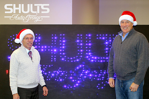 (L to R) Greg Lindquist, executive director for the Jamestown Renaissance Corporation, and Tim Shults, president of Shults Auto Group. The two pose with a handmade LED prop to be used in the Tinseltown Christmas Parade.