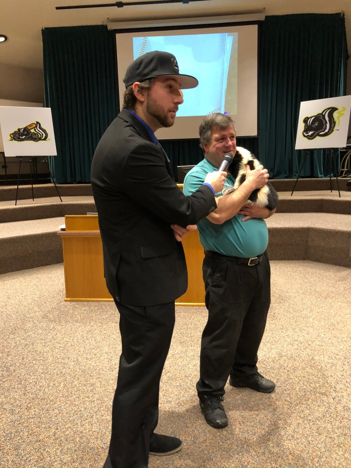 Jamestown Tarp Skunks general Manager, Frank Fanning and Matt from the Hawk Creek Wildlife center in East Aurora with Rascal, the Skunk.