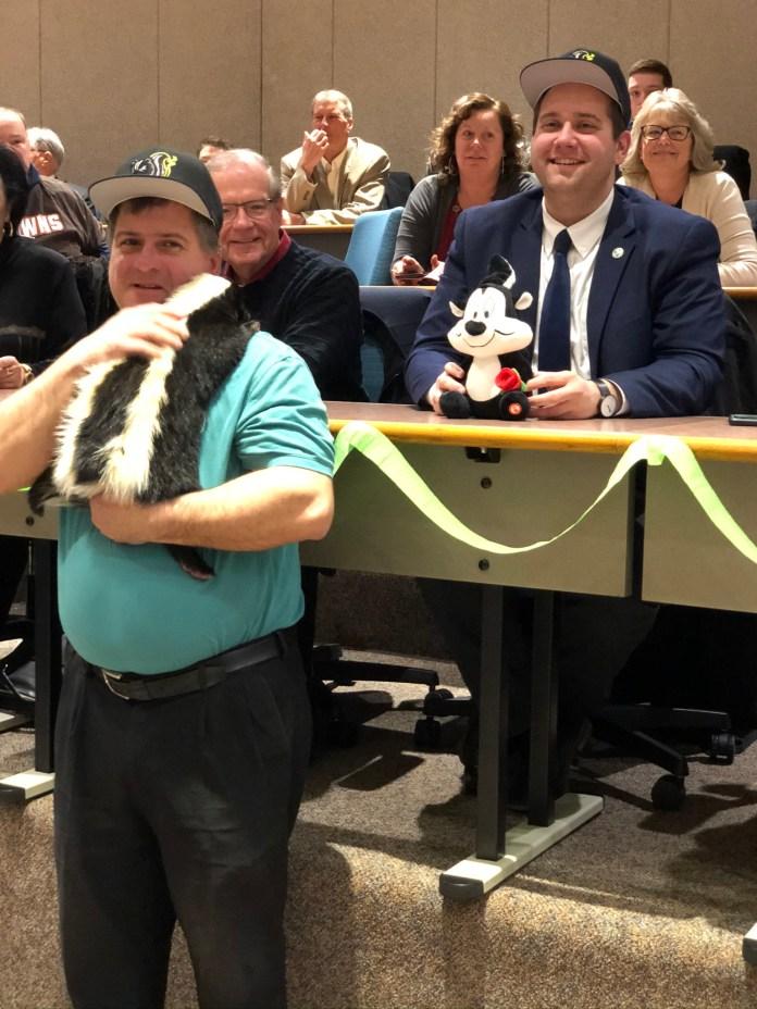 Mayor Eddie Sunquist and Matt from the Hawk Creek Wildlife center in East Aurora with Rascal, the Skunk.
