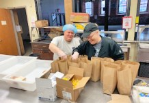 Michelle Knapp, St. Susan Center employee, and Frank Smith, long-time St. Susan Center volunteer, pack meals to serve local residents in need during the coronavirus outbreak. A recent grant from the Chautauqua County Crisis Response Fund will assist St. Susan Center in packing to-go meals.
