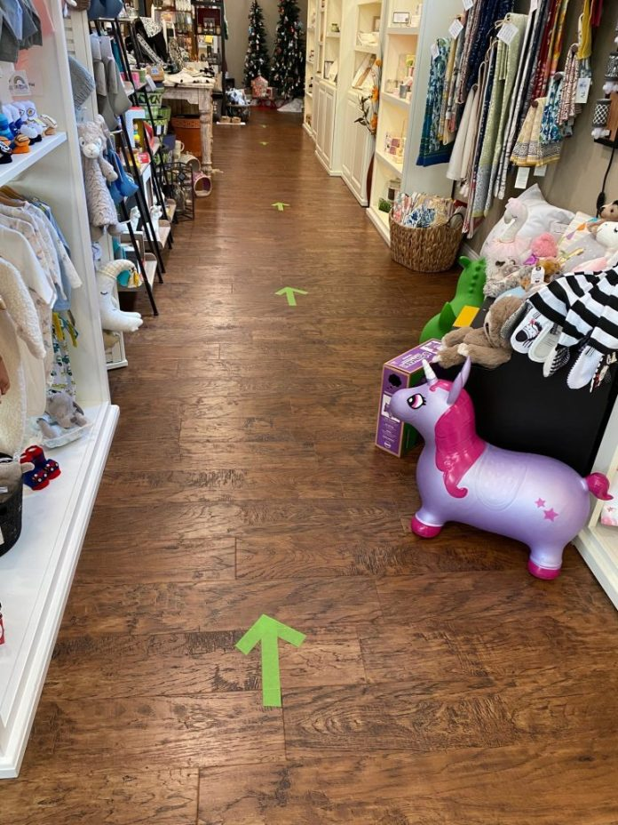 Green arrows lead shoppers around Dot's Gift Boutique to promote social distancing.