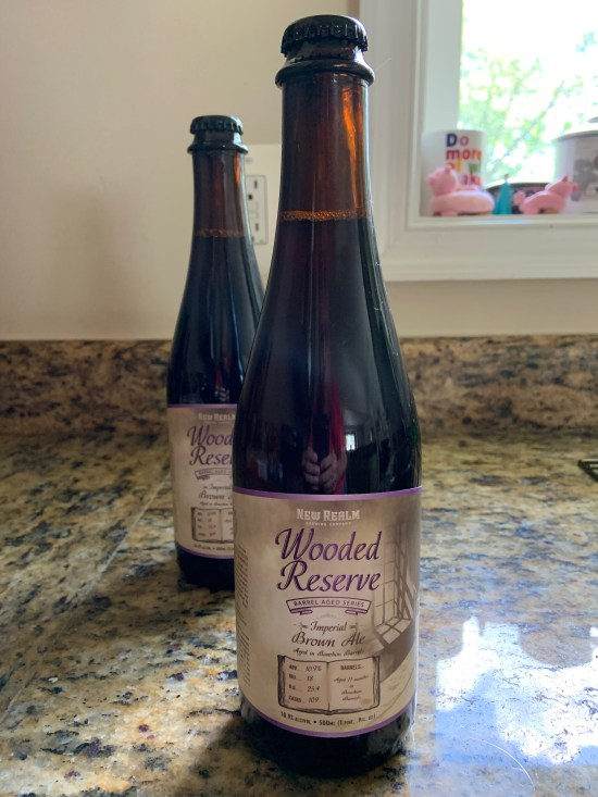 Two bottles of New Realm Wooded Reserve barrel aged brown ale.